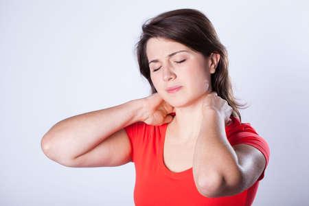夜の後に首の痛みを持つ若い女性