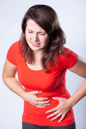 Woman wearing red shirt having terrible stomachache