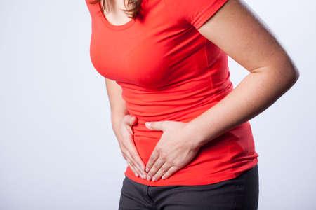 dolor de estomago: Muchacha que tiene la menstruación que sufren de dolor menstrual