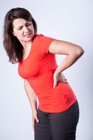 dolor de espalda: De pie mujer joven que tiene dolor de espalda crónico