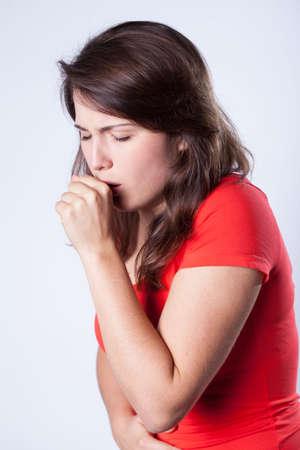 toser: Primer plano de la tos niña sobre fondo gris Foto de archivo