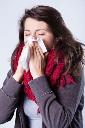 Woman in scarf sneezing and using tissue