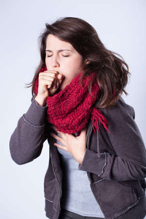 Coughing girl in scarf having high fever
