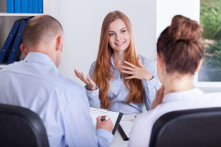 La muchacha habla acerca de su experiencia para una entrevista de trabajo