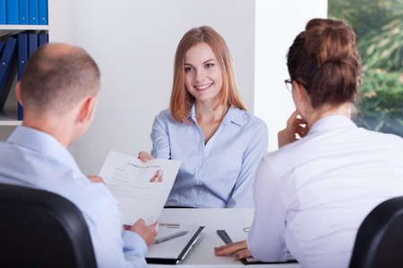 business interview: Young girl gives her CV to employers Stock Photo