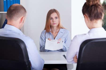 entrevista de trabajo: Muchacha preocupante muestra su CV en una entrevista de trabajo