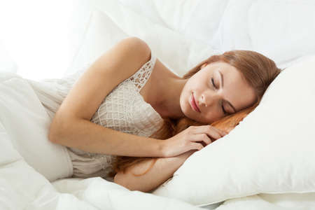 peacefully: Young beautiful woman sleeping peacefully in bed