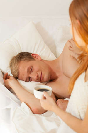 truelove: Women brings coffee to her sleeping husband Stock Photo