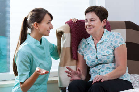 sick person: Young beautiful nurse talking with her older patient