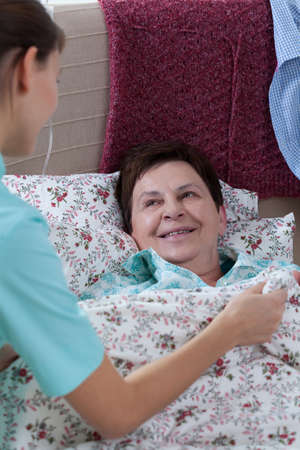 caring nurse: Sick older woman in bed and her caring nurse Stock Photo