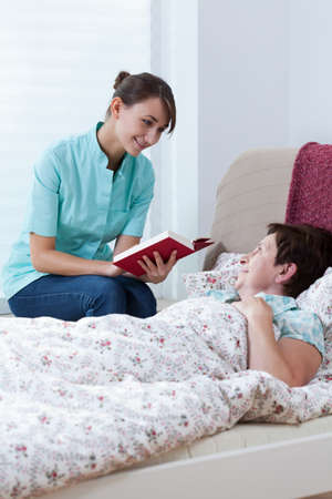 caring nurse: Young caring nurse reading the book to her patient