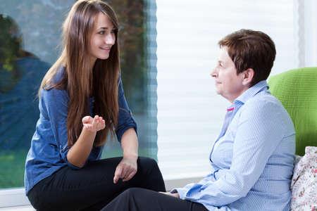amigas conversando: Cuidador bastante joven que visita a su paciente
