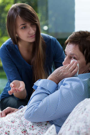bedridden: Worried ill woman and her caring daughter Stock Photo