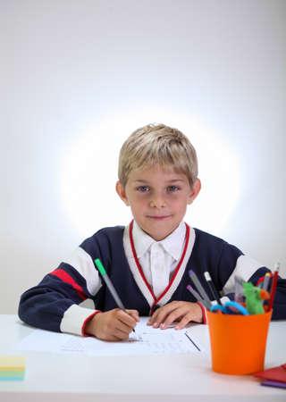 Vertical view of blonde schoolkid doing homework photo