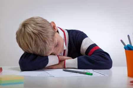 fineliner: Horizontal view of schoolboy sleeping at the desk
