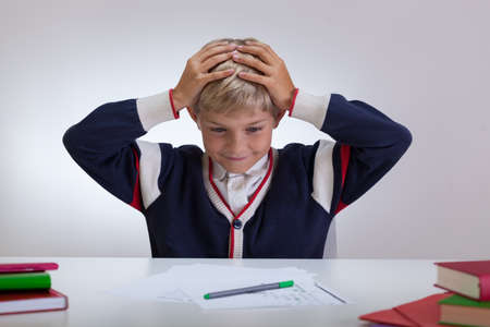 fineliner: Schoolchild cant doing his homework touching his head