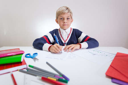 Schoolchild at the sweater doing wordsearch at the desk photo