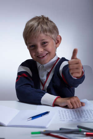 Little schoolboy sitting at the desk showing thumb up