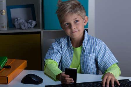 blond boy: Modern blonde child using phone and computer
