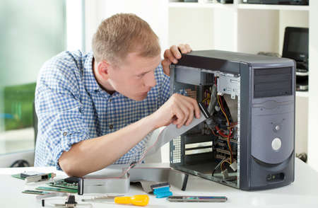 his: Young attractive computer specialist reparing computer in his office