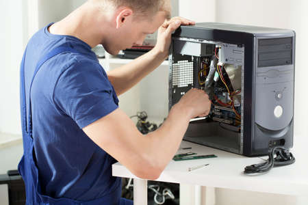 Young smart computer specialist working on broken dismalted computer