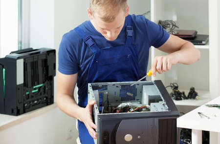 dismantled: Young handsome man trying to repair his broken computer Stock Photo