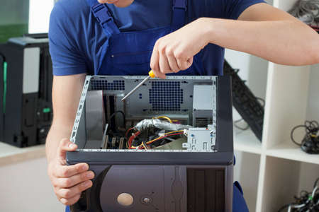 Close-up of mans hands who is trying to repair computer Stock Photo