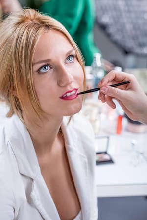 visagiste: Artists hand putting lipstick during wedding makeup