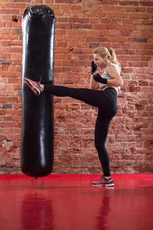 Young strong girl kicking punching bag during her training