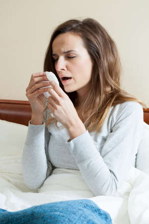 catarrh: Young woman sitting upright in bed sneezing Stock Photo