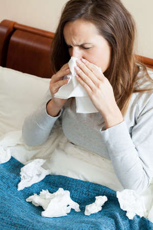 catarrh: Woman with runny nose and a lot of tissues Stock Photo