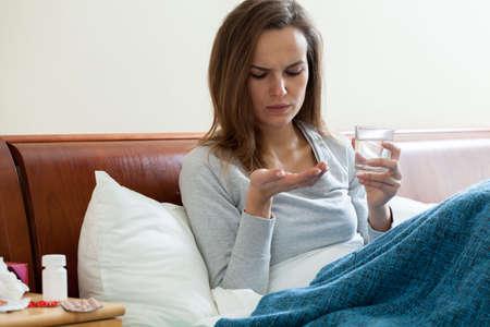 catarrh: Sick woman lying in bed taking medicine Stock Photo