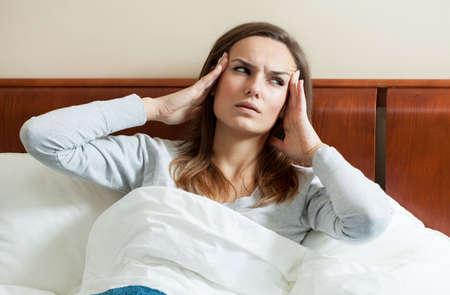 cabeza de mujer: Imagen de la mujer que tiene migra�a acostado en la cama
