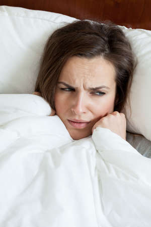 catarrh: Face of sick woman lying under duvet