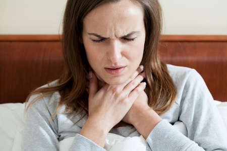 Woman having a sore throat lying in bed