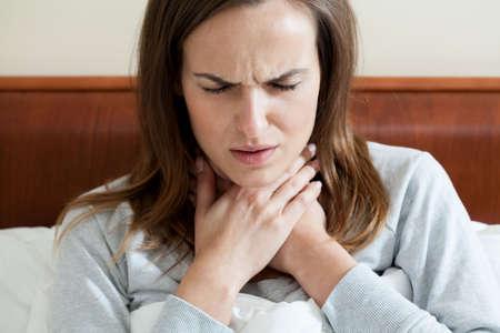 pharyngitis: Woman having a sore throat lying in bed