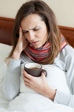 catarrh: Lying woman in scarf having high fever Stock Photo
