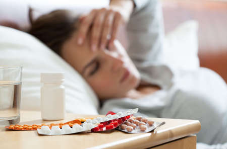 woman at night: A lot of medicines on night table in bedroom Stock Photo