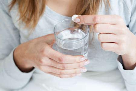 アスピリンを服用病気の女性の水平方向のビュー