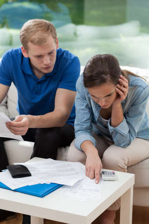 Couple sitting on sofa and analyzing home budget Stock Photo