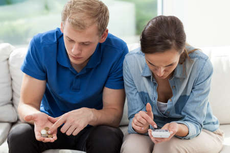 Poor couple sitting on the couch and counting money Stock Photo