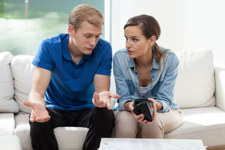 money problems: Horizontal view of couple having empty wallet