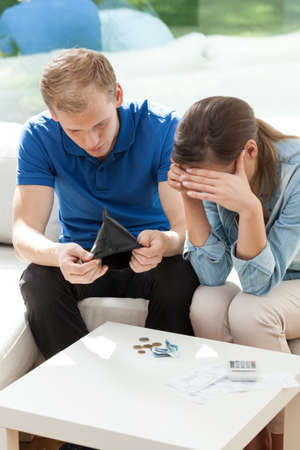 Married couple in bankrupt sitting on the couch photo