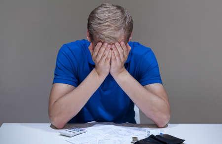 Somber man en onbetaalde rekeningen liggen op het bureau