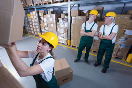 stockroom: Hardworking woman and lazy co-workers in warehouse