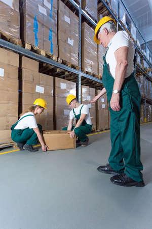 storeroom: Senior warehouse worker controlling young co-workers in storeroom