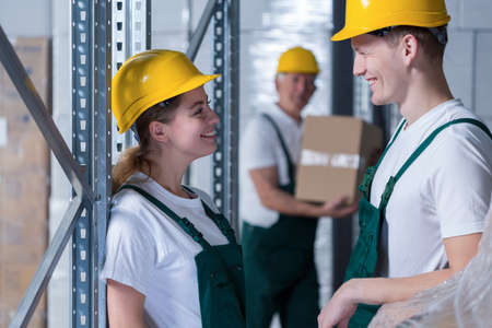 stockroom: Young storage workers flirting together in workplace