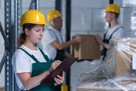 stockroom: Female engineer controlling work in manufacturing plant