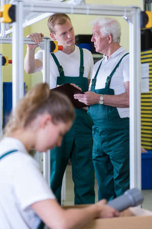 Employees in uniforms working on production hall