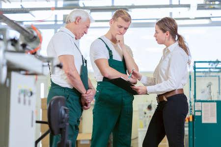 Angry manager beheersen medewerkers in fabriek Stockfoto